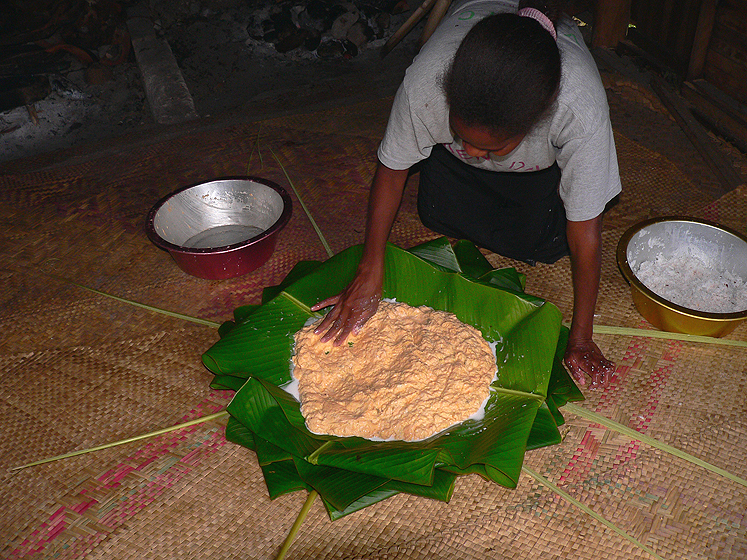 The leaves are folded and splashed with coconut milk before the banana paste is added. People often add pieces of meat on top of the laplap.